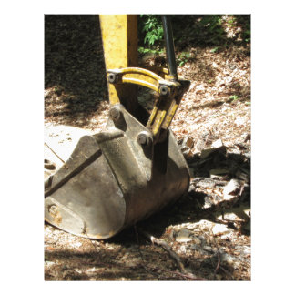 The bucket of the excavator sits at rest letterhead