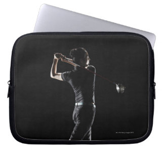 The lady golfer swings the driver of golf computer sleeve