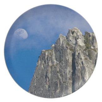 The moon rises and shines through the clouds dinner plate