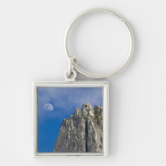 The moon rises and shines through the clouds keychain