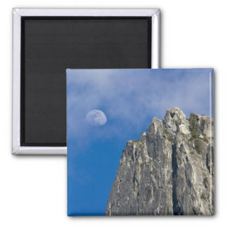 The moon rises and shines through the clouds fridge magnet