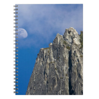 The moon rises and shines through the clouds notebook