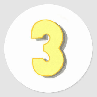 The number three in yellow on round stickers