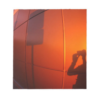 The shadow of a man on a red-orange wall, who phot notepad