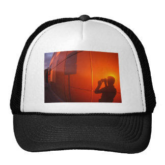 The shadow of a man on a red-orange wall, who phot trucker hat