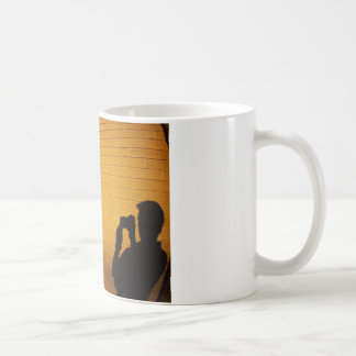 The shadow of a man on the illuminated wall of a h coffee mug