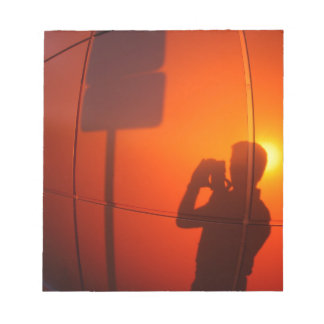 The silhouette of a man on a red-orange wall notepad