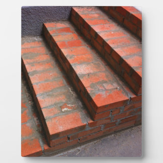 The steps of a new red brick staircase plaque