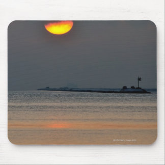 The sun emerges through an off-shore fog bank mouse pad