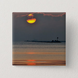 The sun emerges through an off-shore fog bank pinback button