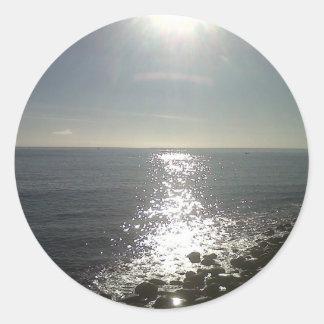 the sun rising over the sea classic round sticker