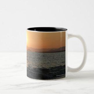 The sun sets over a beautiful mountain range, Two-Tone coffee mug