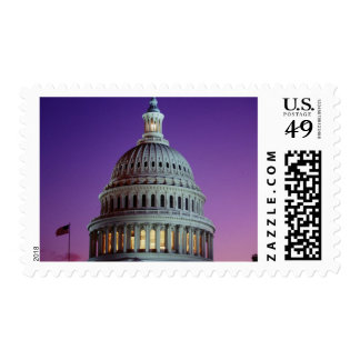The U.S. Capitol at dusk with light in the dome Postage