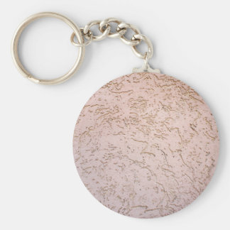 The uneven surface of the wall of gray-pink color basic round button keychain
