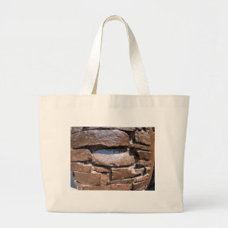 The wall of the large natural stone, painted brown large tote bag