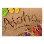 The word Aloha written on a sandy beach, with 2 Card