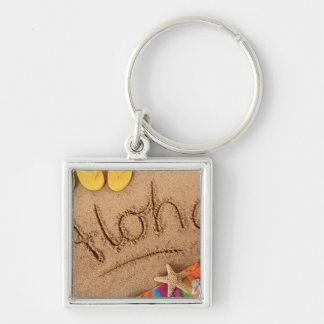 The word Aloha written on a sandy beach, with 2 Silver-Colored Square Keychain