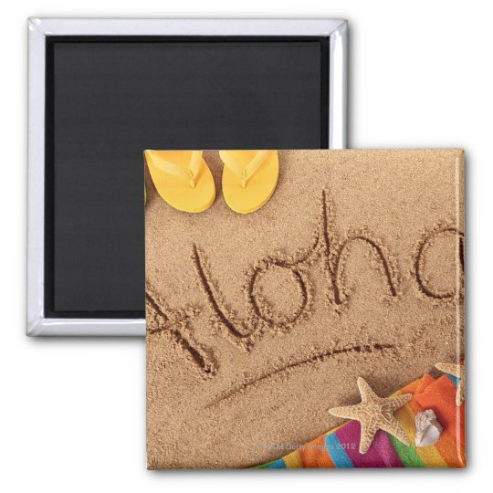 The word Aloha written on a sandy beach, with 2 Magnet