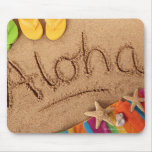 The word Aloha written on a sandy beach, with 2 Mouse Pad