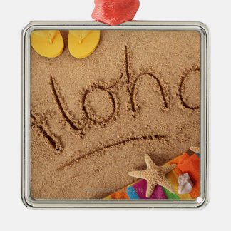 The word Aloha written on a sandy beach, with 2 Square Metal Christmas Ornament