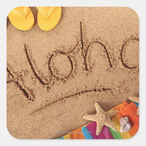 The word Aloha written on a sandy beach, with 2 Sticker