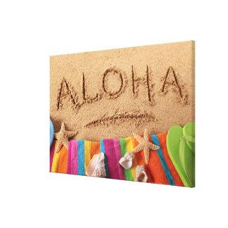 The word Aloha written on a sandy beach, with Canvas Print