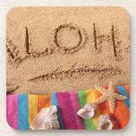 The word Aloha written on a sandy beach, with Drink Coaster