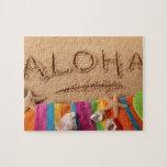 The word Aloha written on a sandy beach, with Jigsaw Puzzle