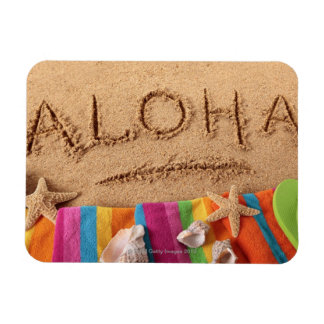 The word Aloha written on a sandy beach, with Magnet