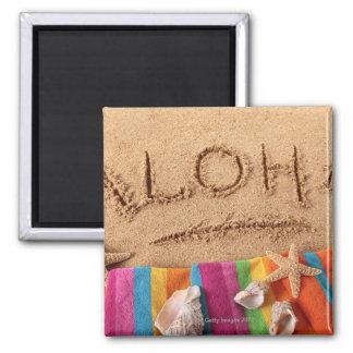 The word Aloha written on a sandy beach, with Magnet