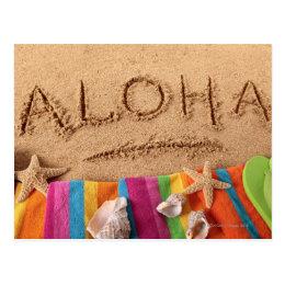The word Aloha written on a sandy beach, with Postcard