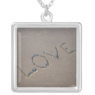The word Love spelled out in the sand. Silver Plated Necklace