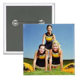 Three cheerleaders forming human pyramid on 2 inch square button