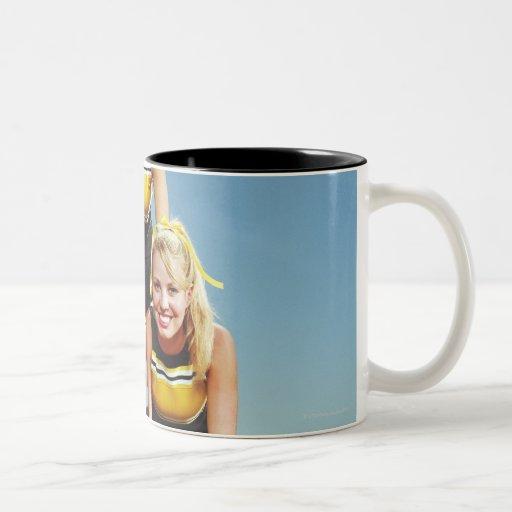 Three cheerleaders forming human pyramid on coffee mug
