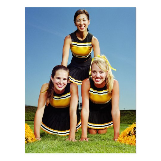 Three cheerleaders forming human pyramid on postcard