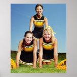 Three cheerleaders forming human pyramid on poster