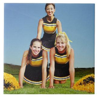 Three cheerleaders forming human pyramid on tile