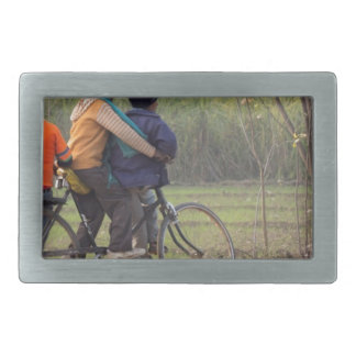 Three children on a cycle at the side of the road rectangular belt buckles