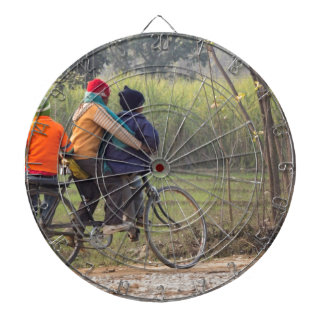 Three children on a cycle at the side of the road dartboard