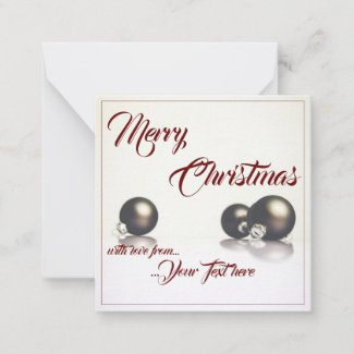 Three christmas balls in front of light background note card