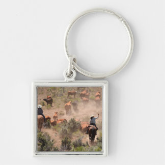 Three cowboys and cowgirls driving cattle keychain