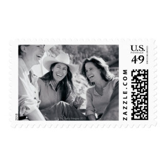 Three cowgirls laughing together postage