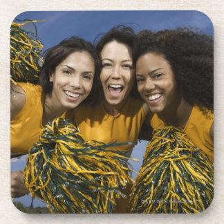 Three female cheerleaders holding pompoms beverage coaster