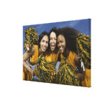 Three female cheerleaders holding pompoms gallery wrapped canvas