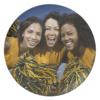 Three female cheerleaders holding pompoms dinner plates