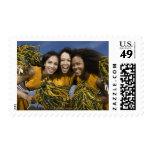 Three female cheerleaders holding pompoms postage