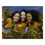 Three female cheerleaders holding pompoms poster
