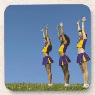 Three female cheerleaders standing in row beverage coaster