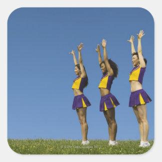 Three female cheerleaders standing in row square sticker