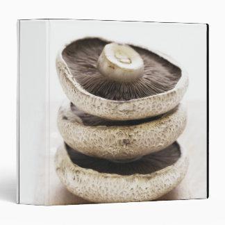Three flat mushrooms in pile on wooden board 3 ring binders